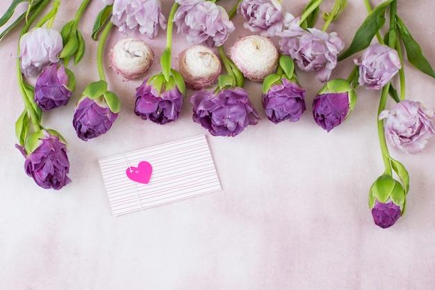 Une rangée sont des tulipes pourpres et une enveloppe avec un coeur