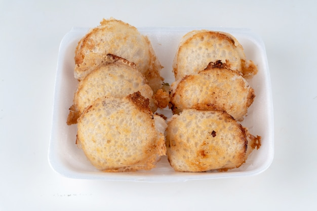 Rangée de sorte de friandises thaïlandaises dans un plat en mousse sur un fond blanc.