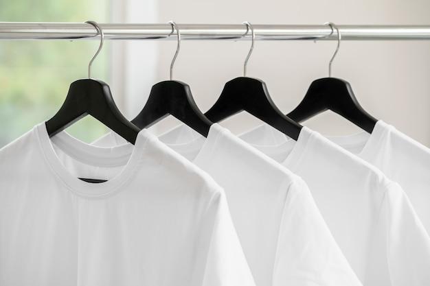 Rangée de t-shirts blancs sur des cintres accrochés au rack