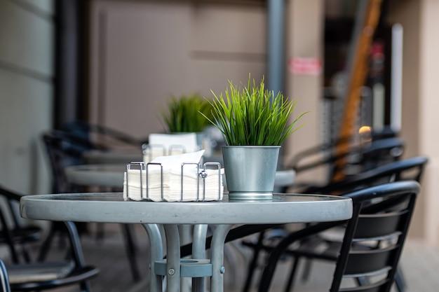 Une rangée de tables avec des chaises passe dans une rue floue