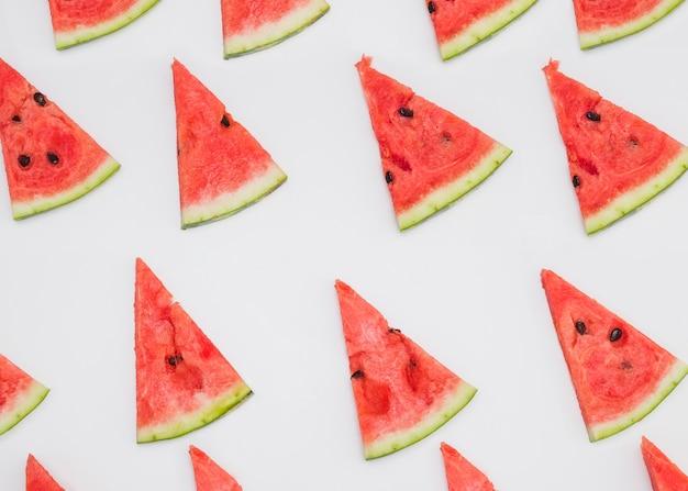 Rangée de tranches de melon d'eau triangulaires sur fond blanc