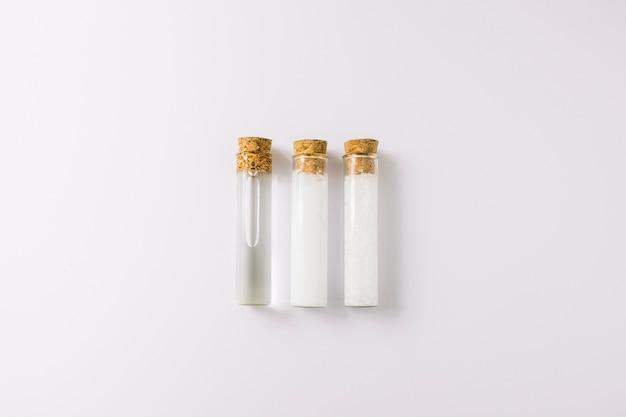 Rangée de trois huiles essentielles dans des éprouvettes sur fond blanc