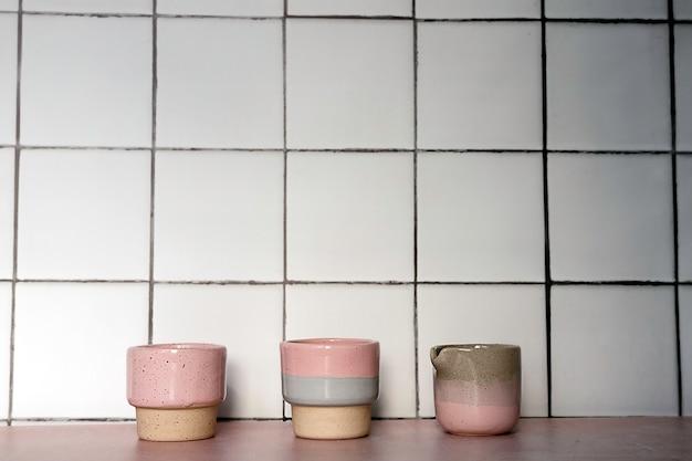 Une rangée de trois tasses en céramique faites à la main sur un fond de carreaux de cuisine blancs avec des ombres.
