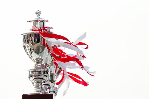 Rangée de trophée de la coupe à égalité avec ruban blanc et rouge sur fond blanc