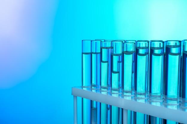 Rangée de tubes à essai avec des liquides sur un fond bleu et vert