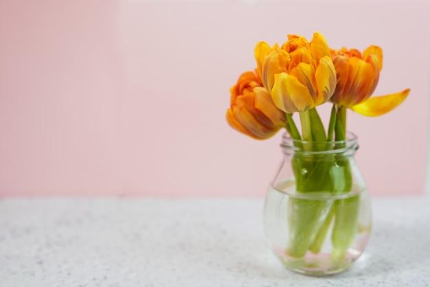 Rangée de tulipes dans un vase sur fond coloré avec espace pour le message. fond de fête des mères.