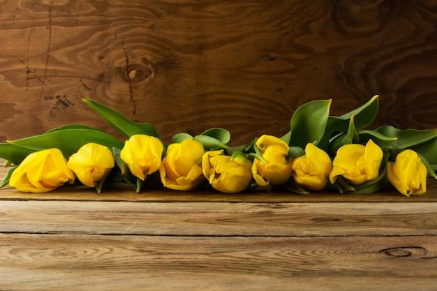 Rangée de tulipes jaunes sur fond en bois, espace copie