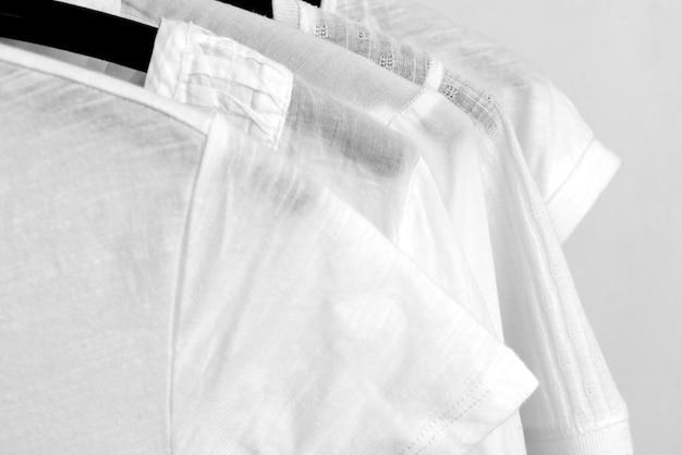 Une rangée de vêtements en coton blanc pend sur des cintres noirs sur une étagère dans un magasin.