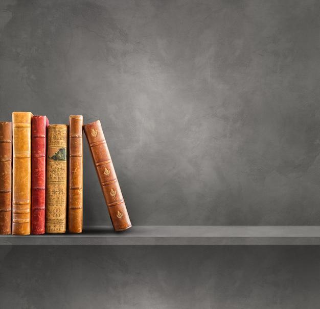 Rangée de vieux livres sur une étagère grise. fond de scène carrée