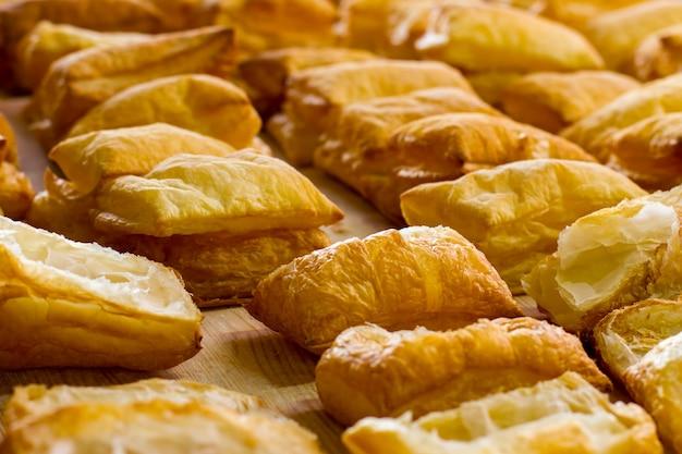 Des rangées de bouffées jaunes. pâtisserie sur planche de bois clair. les revenus de la boulangerie augmentent. pâte aérée sucrée.