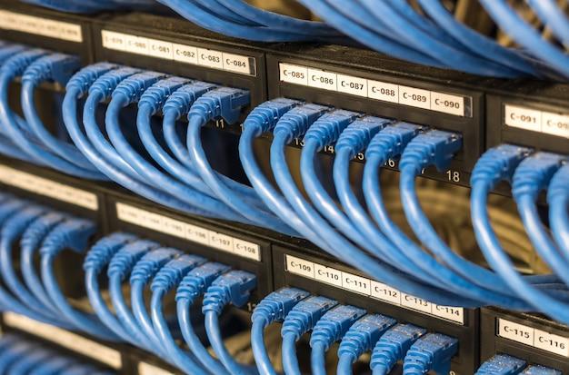 Rangées de câbles réseau connectés au routeur et au commutateur dans la salle des serveurs