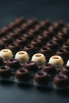 Des rangées de coquilles de truffes au chocolat noir et blanc faites maison avec différentes garnitures. mise au point sélective