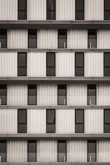 Rangées de fenêtres vitrées et garde-corps en verre d'un bâtiment urbain minimaliste en noir et blanc