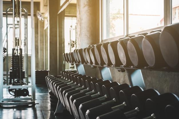 Des rangées d'haltères dans le fond de la salle de gym pour la présentation de la bannière. thèmes sur l'exercice pour une bonne santé.