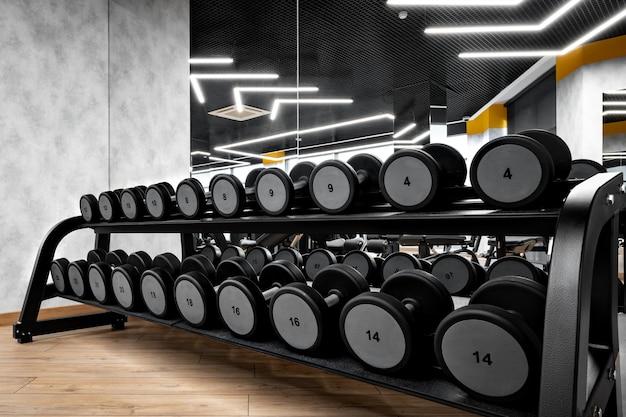 Rangées d'haltères métalliques sur rack pour la musculation en salle de sport