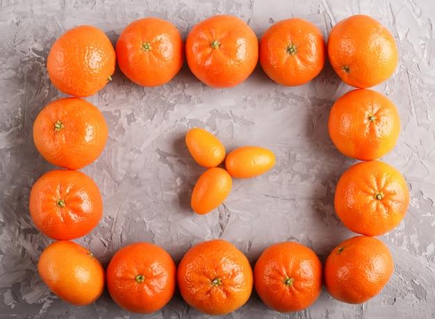 Rangées de mandarines formant un rectangle et trois kumquats à l'intérieur, vue de dessus.