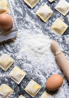 Rangées de raviolis crus faits maison avec des ingrédients, gros plan et vue de dessus