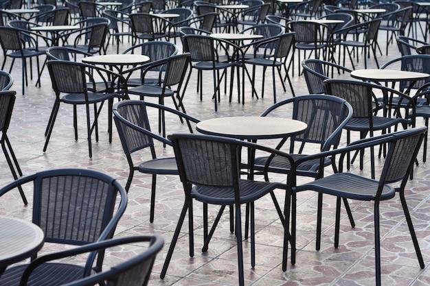 Des rangées de tables avec des chaises à l'extérieur de l'hôtel