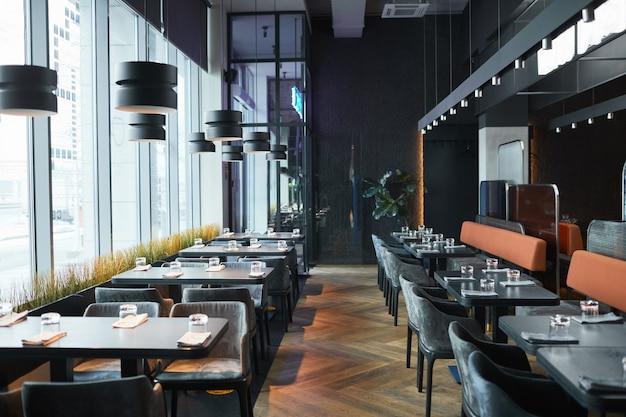 Des rangées de tables et de chaises de restaurant dans une pièce grise avec des lampes en forme de cylindre
