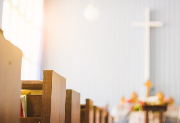 Rangées vides de banc de bois dans l'église. mise au point sélective, avec fond croisé et gradient