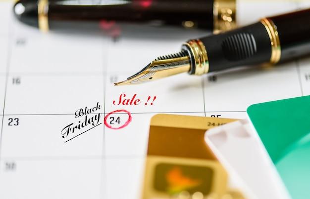 Rappel black friday vente en calendrier blanc avec stylo noir et cartes de crédit