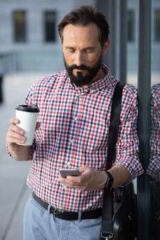 Rappeler. agréable homme sérieux, boire du café en tapant un message