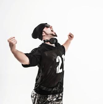 Le rappeur avec des écouteurs interprète une chanson de rap sur fond blanc.