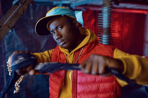 Rappeur élégant en sweat à capuche jaune posant avec une décoration underground cool. artiste hip-hop, chanteur de rap, performance de break-dance