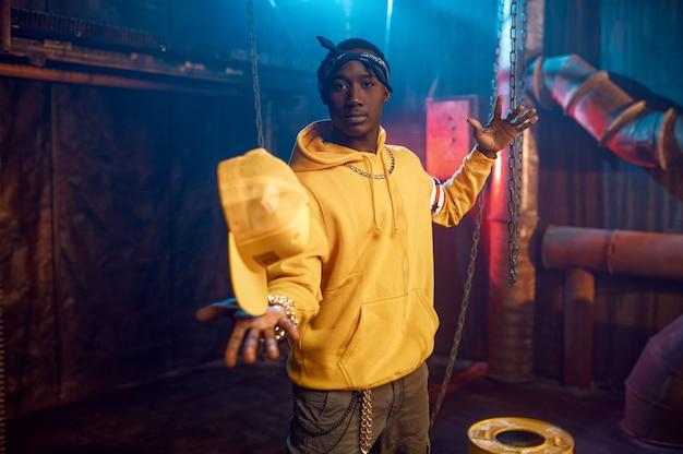 Le rappeur élégant en sweat à capuche jaune pose en studio avec une décoration underground cool