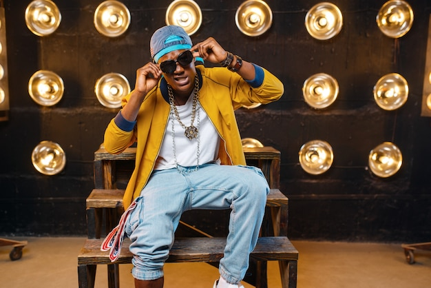 Rappeur noir en casquette et lunettes de soleil assis sur les marches, chanteur sur scène avec des projecteurs sur le mur. interprète de rap sur scène avec lumières, musique underground, style urbain