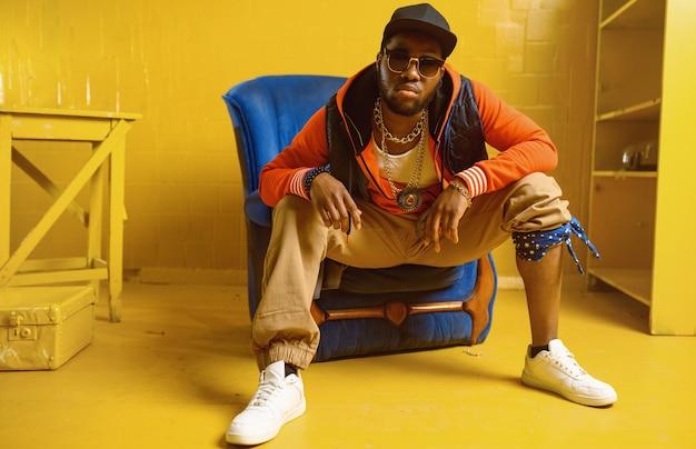 Rappeur souriant posant dans la chaise avec des tons jaunes. artiste hip-hop, chanteur de rap, performance de break-dance