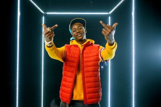 Rappeur souriant sur scène avec cube lumineux. artiste de hip-hop, chanteur de rap, spectacle de break-dance, mode de vie de divertissement
