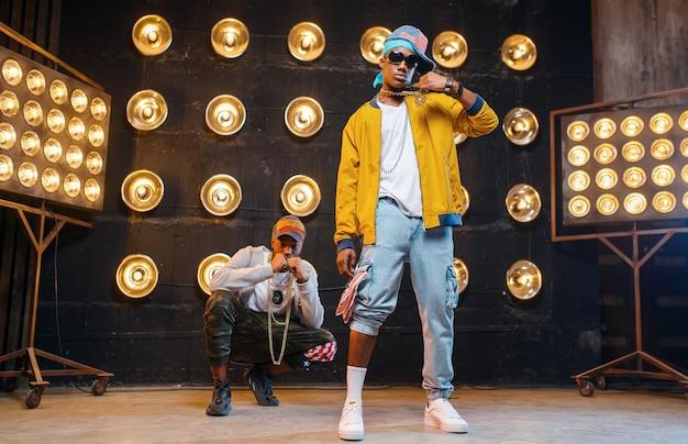 Des rappeurs en casquettes dansent sur scène avec des projecteurs