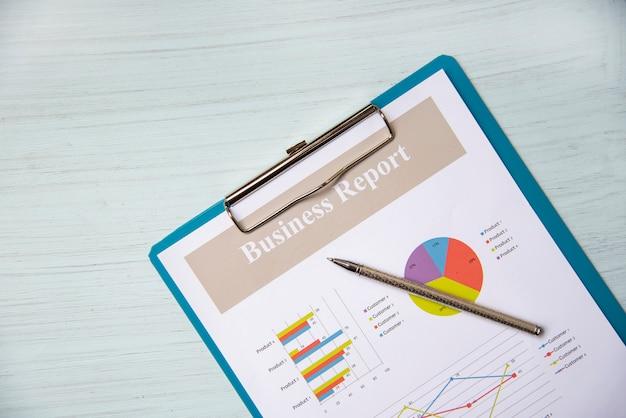 Rapport d'activité graphique graphique et stylo sur le document de rapport papier présent financier