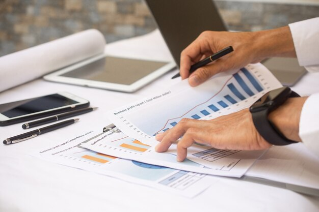 Rapport sur les bénéfices de l'entreprise travaillant à la main au bureau d'affaires