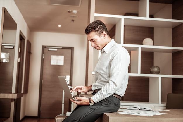 Rapport de finition. homme aux cheveux noirs finissant son rapport mensuel avant d'aller à la réunion