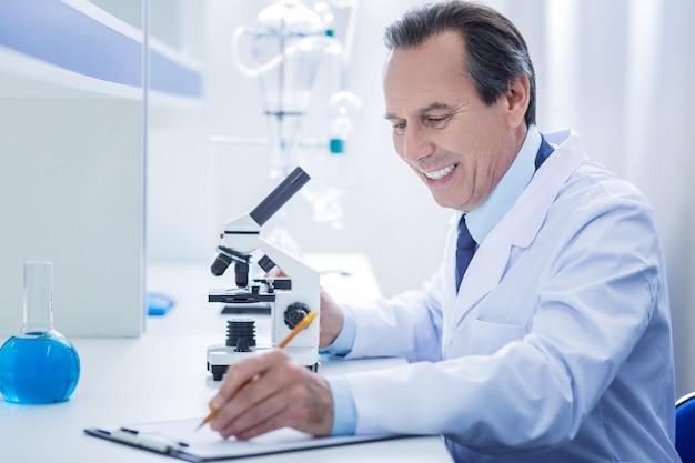 Rapport sur la recherche. heureux homme gentil positif assis à la table et écrivant ses observations tout en terminant un rapport