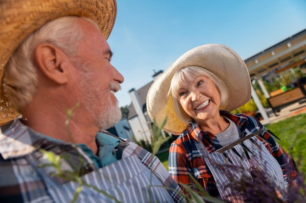 Rapports. agréable gentil homme et femme souriant tout en se regardant