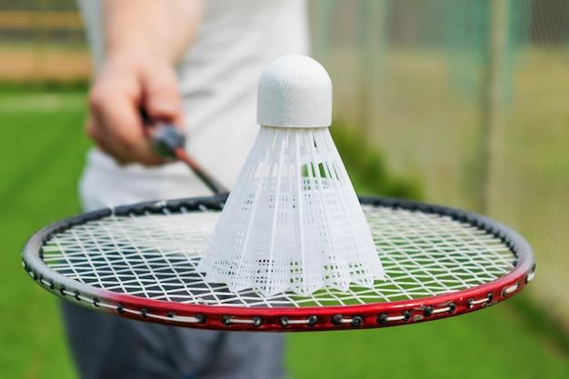 Raquette de badminton dans la main d'un homme vêtu d'un t-shirt blanc.