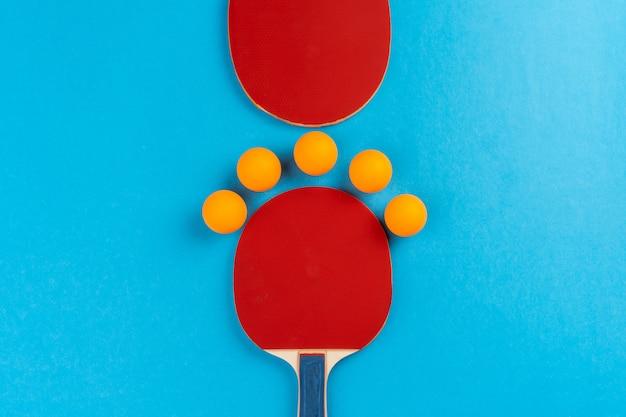 Raquette de ping-pong et balle sur fond bleu
