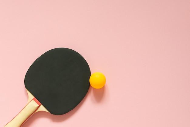 Raquette de ping-pong de tennis noir isolé sur un mur rose, équipement de sport pour le tennis de table