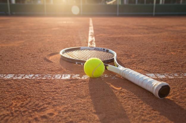 Une raquette de tennis et une balle placées sur le terrain.