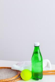 Raquette de tennis et bouteille d'eau avec serviette