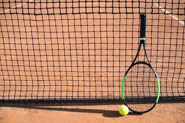 Raquette de tennis grand angle reposant sur le filet de tennis