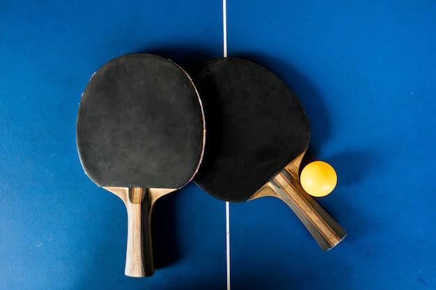 Raquette de tennis de table et balle sur fond bleu.