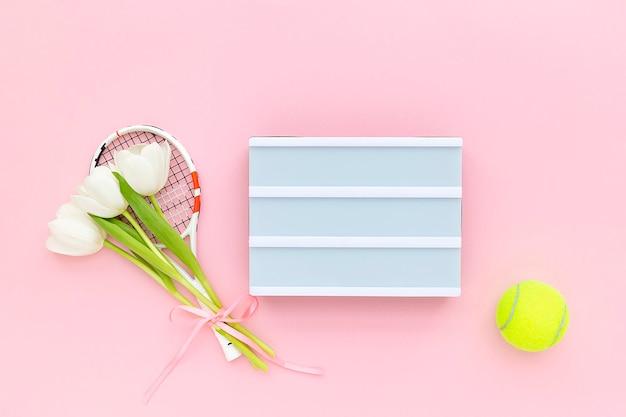 Raquette de tennis avec tulipes blanches, balle de tennis et caisson lumineux pour texte sur fond rose pastel