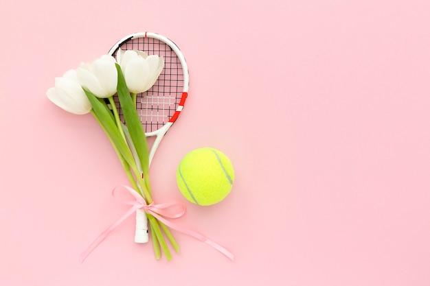 Raquette De Tennis Avec Tulipes Blanches Et Balle De Tennis Sur Fond Rose Pastel Avec Espace De Copie Photo Premium