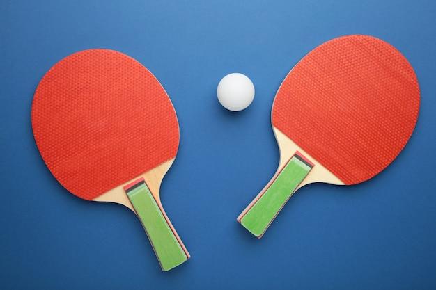 Raquettes de ping-pong et balle sur fond bleu. vue de dessus