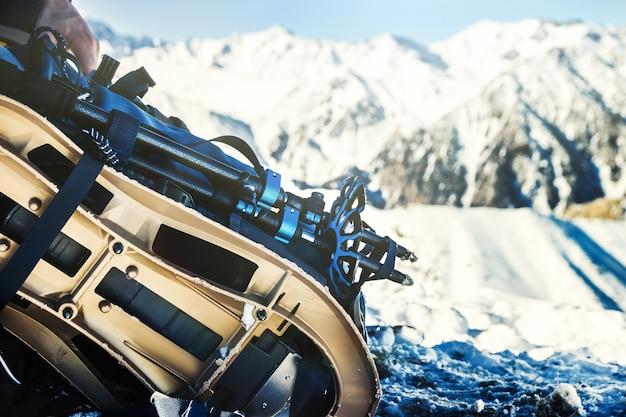 Raquettes de sac à dos en gros plan et bâtons de randonnée contre un paysage enneigé aventure de sports d'hiver