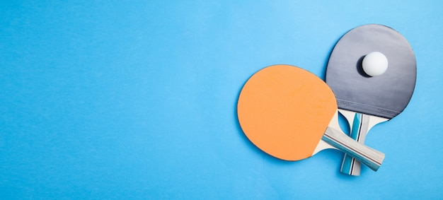 Raquettes de tennis de table et une balle en plastique blanche sur fond bleu.